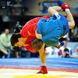 """ITAR-TASS: MOSCOW, RUSSIA. JUNE 7, 2013. Igor Beglerov of Russia (red) and Dzhambulat Akhmadov of Belarus fight in the men's -52kg match during the President's Sambo Cup at Druzhba Arena in Moscow. (Photo ITAR-TASS / Zurab Dzhavakhadze) Ðîññèÿ. Ìîñêâà. 7 èþíÿ. Áåëîðóññêèé ñïîðòñìåí Äæàìáóëàò Àõìàäîâ (â ñèíåì) è ðîññèéñêèé ñïîðòñìåí Èãîðü Áåãëåðîâ (â êðàñíîì) âî âðåìÿ áîÿ â êàòåãîðèè äî 52 êã â ÓÑÇÊ """"Äðóæáà"""". Ôîòî ÈÒÀÐ-ÒÀÑÑ/ Çóðàá Äæàâàõàäçå"""
